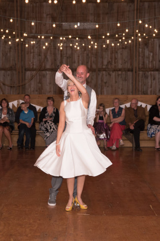 Bride and groom dancing in barn wedding reception