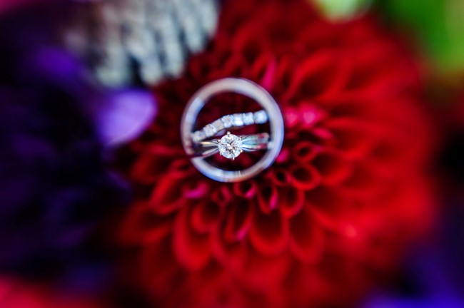 Round diamond solitaire engagement ring on a red flower with diamond wedding band