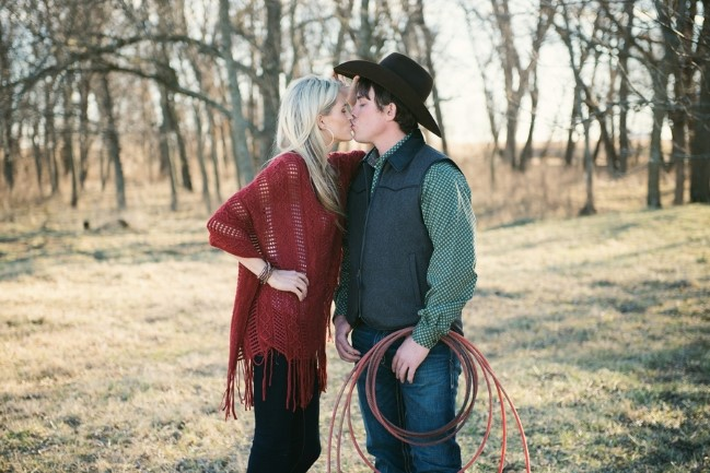 Engaged couple kissing outside with guy holding a lasso