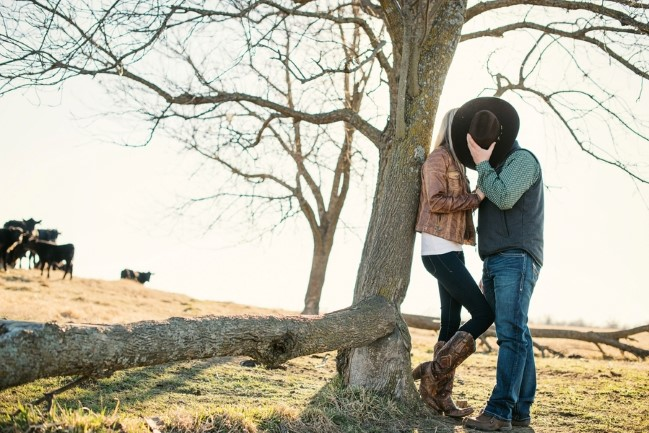 Couple kissing behind a cowboy hat for an engagement shoot