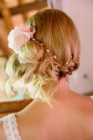 Bride wearing her hair on a side bun with a pink flower
