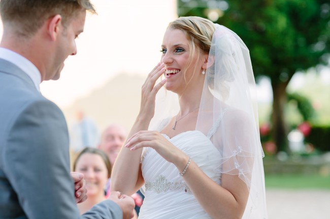 Bride laughing during outdoor wedding ceremony in Tuscany