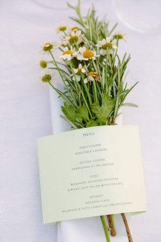 White wild flowers with menu card for wedding reception place setting