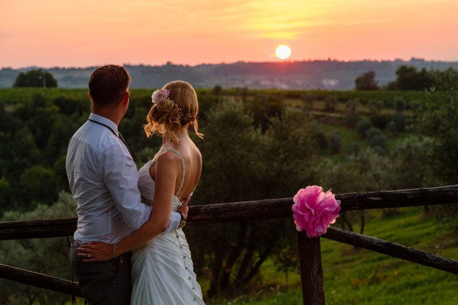 Bride and groom looking out into the sun set captured by Innocenti Studio