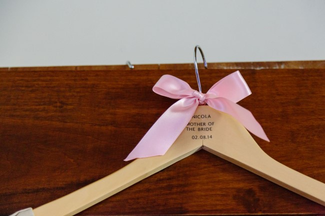 A wooden mother of the bride hanger with a pink bow