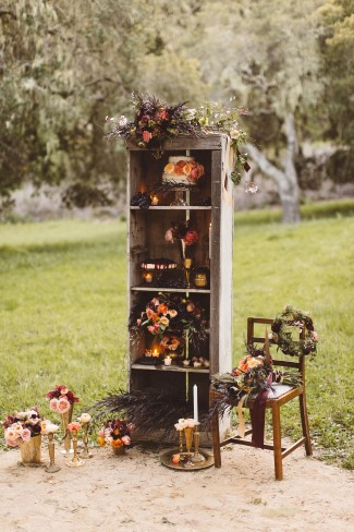 vintage wood bookshelf and chair with flowers and decor in open field