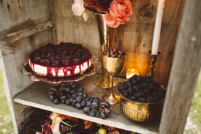 wood bookshelf with filled gold goblets, cheesecake, and grapes