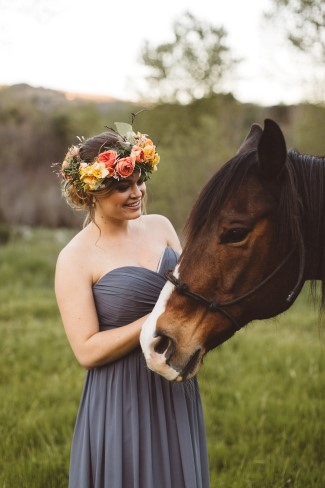bride with flower crown stands next to horse