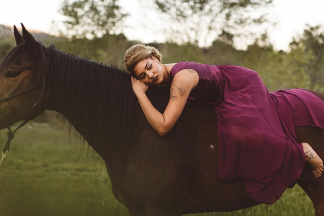 model in purple dress laying on horse's back