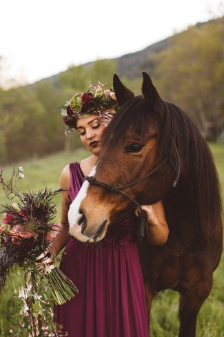 bride holds rein of horse in one hand and bouquet in other hand