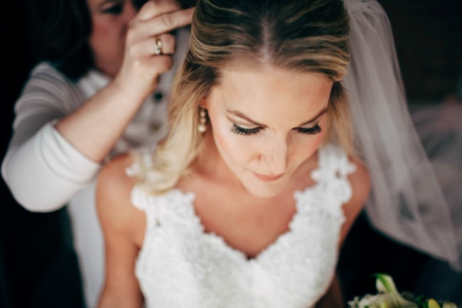 mother of the bride putting the bride's floor length veil in her her hair