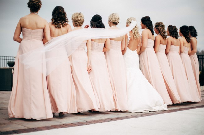 Bride lined up with her bridesmaids wearing blush pink floor length gowns