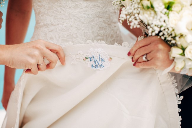 Bride flipping her dress over showing a blue embroidered initials and wedding date