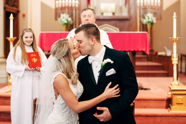 Bride and groom kissing during church ceremony captured by Reese & Renee