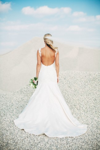 Bride standing in a rock quarry with her back turned to the camera captured by Reese & Renee