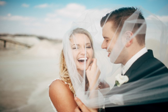 Bride and groom laughing under a chapel length wedding veil