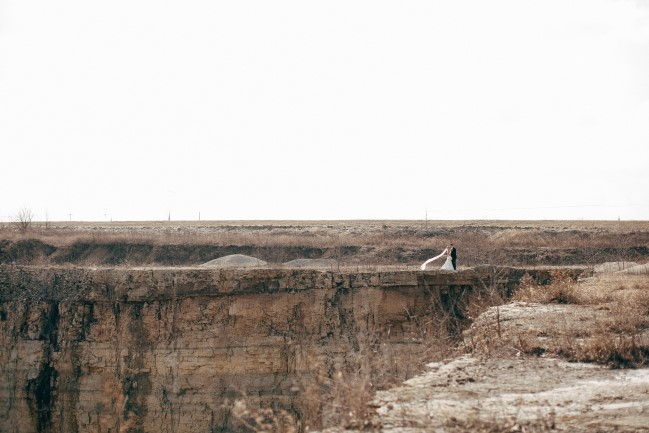 Bride and groom standing on the edge of a rock quarry captured by Reese & Renee