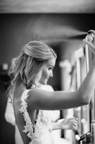 black and white photo of Bride spraying hair spay in her hair