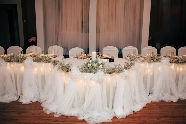 Long wedding reception table with baby's breath and gold charger plates and white candles