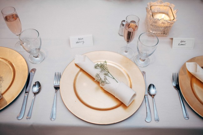 Wedding reception place setting using gold charger, white napkin and baby's breath