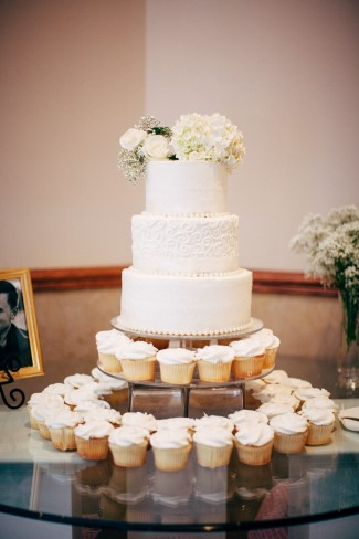 3 tier white wedding cake with 2 tiers of cup cakes underneath created by The Bake Shoppe (