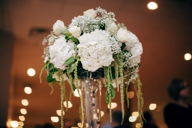 wedding reception floral center piece created by Floral Reflections using white hydrangeas, baby's breath and white roses