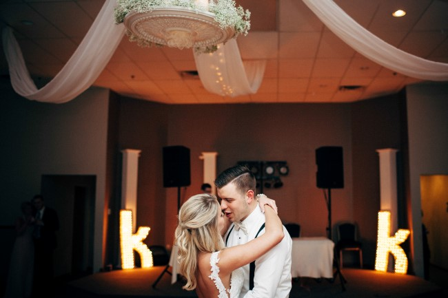 Bride and groom dancing under ballroom chandelier captured by Reese & Renee