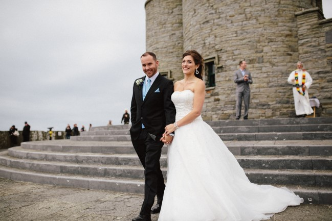 Bride and groom walking down stairs at cliffs of Moher after wedding ceremony