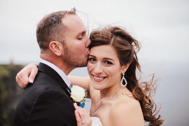 Groom kissing brides forhead. Bride wearing strapless gown and tier drop hoop earrings