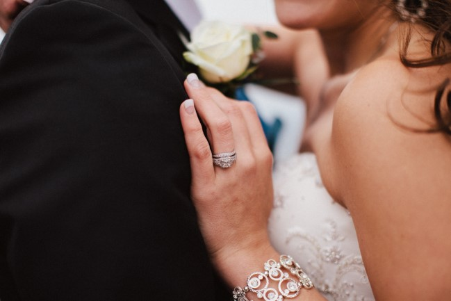 Bride with hand on grooms chest wearing a halo ring