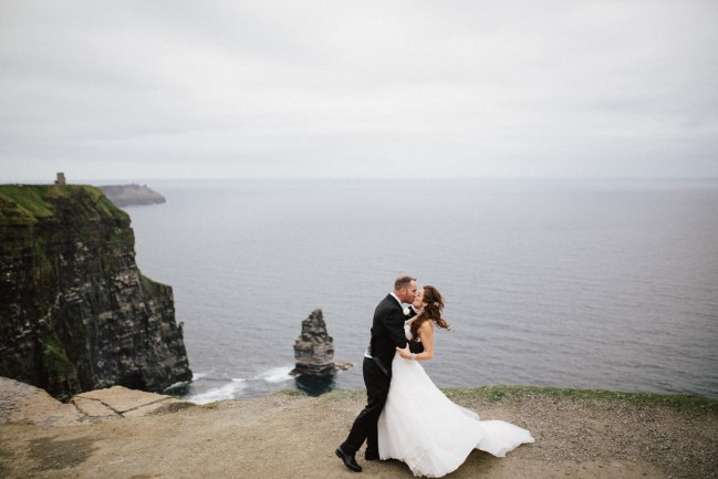Bride and groom kissing on top of Cliffs of Moher