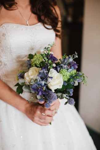 Purple and white bridal bouquet with blue bells, white roses and thistles
