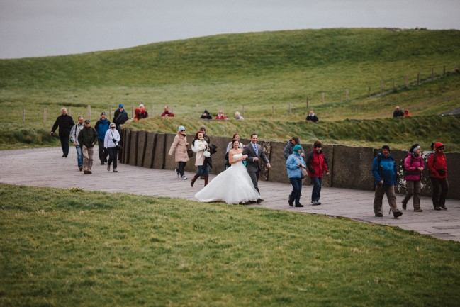 Bride walking up side walk during wedding ceremony at cliffs of moher