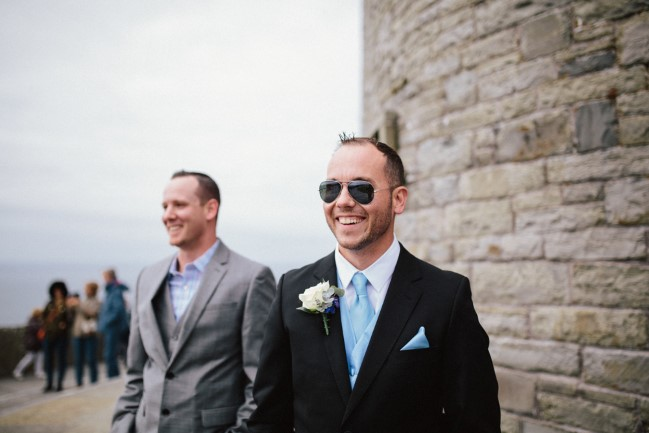 groom wearing black suit and baby blue tie with pocket square