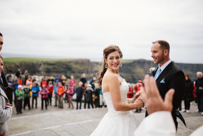 Bride and groom holding hands during wedding ceremony at Cliffs of Moher