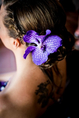 Bride wearing braid and orchid in her hair