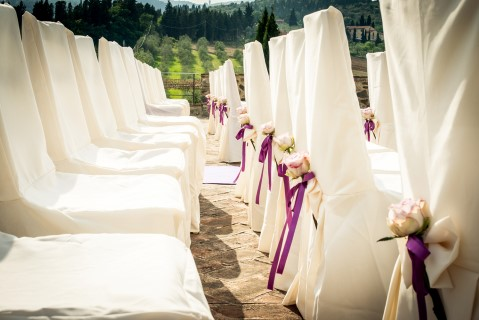 Chairs lined for outdoor wedding ceremony with white chair covers and purple ribbon