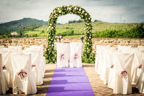 Outdoor wedding ceremony with a purple aisle runner in Tuscany