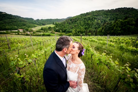 Bride and groom kissing in vineyard in Tuscany captured by Qualcosa di Blu