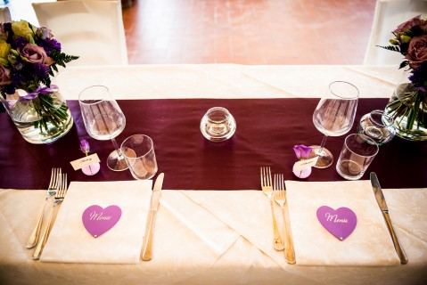 Purple wedding reception themed table with with heart shapes for place cards