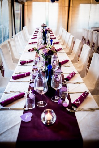 Wedding reception table with purple table runner and purple napkins
