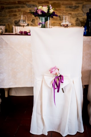 Chair covered with a white chair cover with a purple bow and pink flower at the back