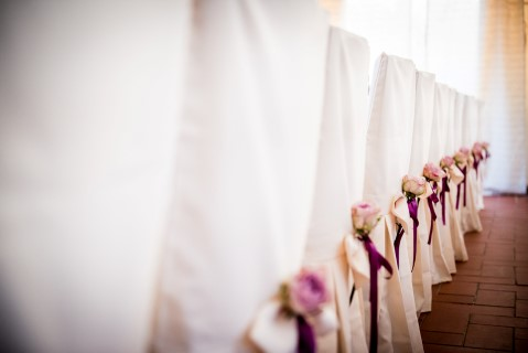 Wedding reception in line with purple bows and pink flowers