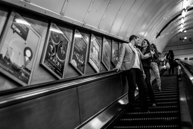 Couple traveling down the escalator in a London Tube Station for an engagement shoot