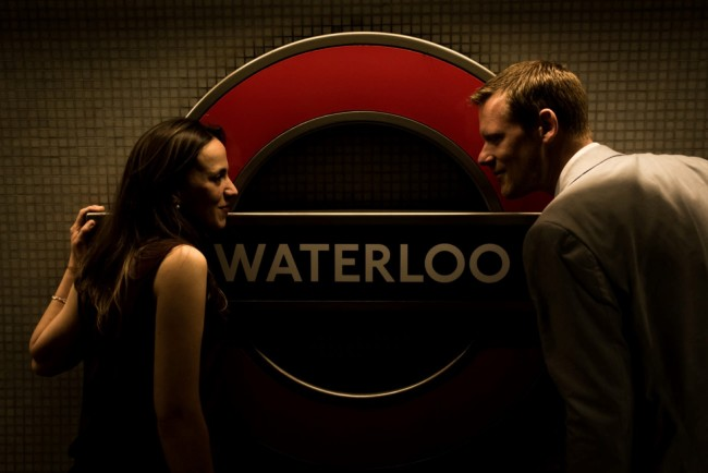 Couple looking at each other in front of the Waterloo Tube station sign for engagement session