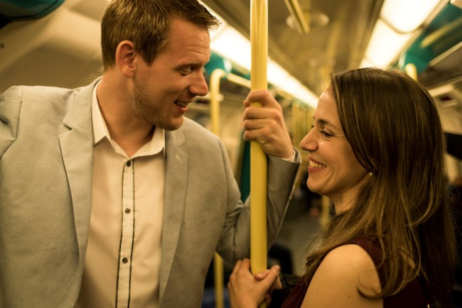 Couple riding the London Tube for engagement shoot
