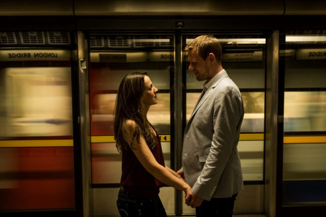 Engaged couple standing facing each other in a London Tube station while train passes captured by Matt Badenoch Photography