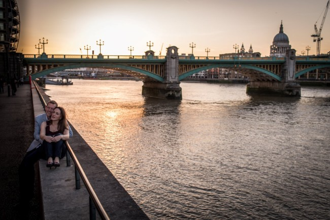 Couple sitting on wall along Thames captured by Matt Badenoch Photography
