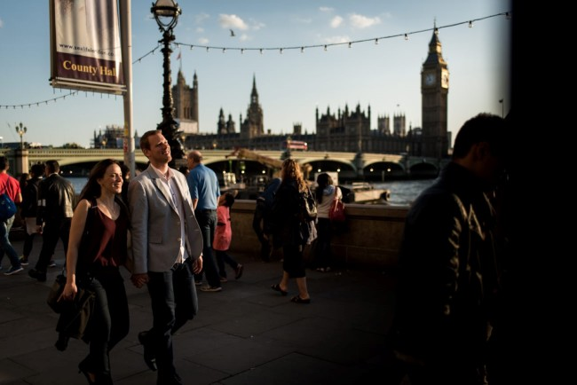 Couple walking hand in hand down the Thames with big Ben in the background