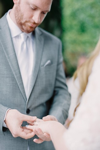 Groom putting ring on bride's finger during outdoor ceremony at Villa Del Balbianello